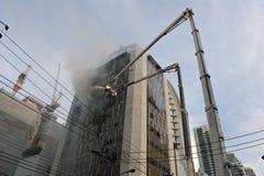 Les sapeurs-pompiers abordent une flamme dans un immeuble de bureaux Image stock
