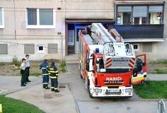 Les sapeurs-pompiers au début de l'action se tiennent avec deux policiers à côté du camion de pompiers Image stock