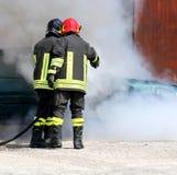 les sapeurs-pompiers avec l'uniforme et le casque de protection s'éteignent photos stock