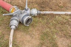 Les sapeurs-pompiers couplant pour l'eau s'éteignante de distribution à plusieurs tuyaux images libres de droits