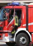 Les sapeurs-pompiers courageux dans l'action sautent vers le bas rapidement du firetruc Image libre de droits