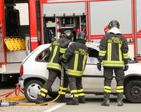 Les sapeurs-pompiers courageux soulagent blessé après un accident de la route photos libres de droits