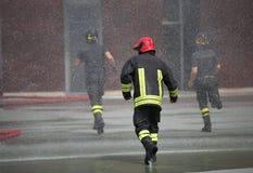 Les sapeurs-pompiers courent rapidement sous éclabousse de l'eau images stock