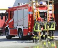 Les sapeurs-pompiers dans l'action prennent l'échelle en bois Photographie stock libre de droits