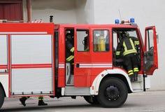 Les sapeurs-pompiers descendent rapidement des firetrucks image stock