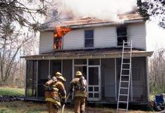 Les sapeurs-pompiers disposent à entrer dans une maison sur le feu photographie stock libre de droits