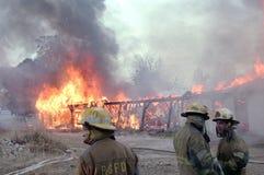 Les sapeurs-pompiers disposent à verser l'eau sur un bâtiment sur le feu image stock
