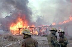 Les sapeurs-pompiers disposent à verser l'eau sur un bâtiment sur le feu images libres de droits