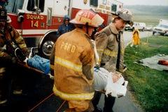 Les sapeurs-pompiers enlèvent une personne blessée d'un accident automobile photographie stock libre de droits