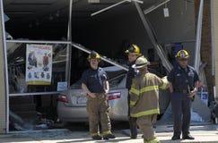 Les sapeurs-pompiers inspectent une voiture qui a conduit par un magasin photographie stock libre de droits