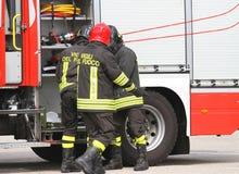 Les sapeurs-pompiers italiens s'approchent du camion de pompiers par la préparation pour éteindre photo stock