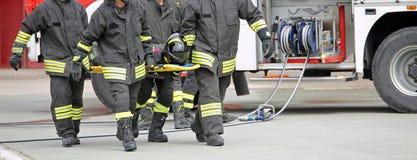 Les sapeurs-pompiers portent une personne blessée photos libres de droits