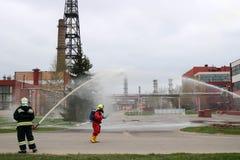 Les sapeurs-pompiers professionnels dans les costumes résistants au feu oranges dans les casques blancs avec des masques de gaz e photo libre de droits