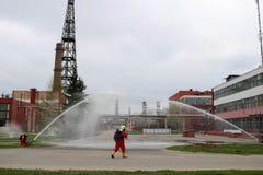 Les sapeurs-pompiers professionnels dans les costumes résistants au feu oranges dans les casques blancs avec des masques de gaz e images libres de droits