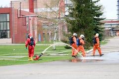 Les sapeurs-pompiers professionnels dans les costumes résistants au feu oranges dans les casques blancs avec des masques de gaz e image stock