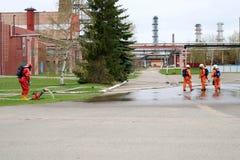 Les sapeurs-pompiers professionnels dans les costumes résistants au feu oranges dans les casques blancs avec des masques de gaz e photographie stock