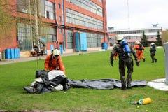 Les sapeurs-pompiers professionnels, les sauveteurs dans les costumes ignifuges protecteurs, les casques blancs et les masques de photo libre de droits