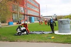 Les sapeurs-pompiers professionnels, les sauveteurs dans les costumes ignifuges protecteurs, les casques et les masques de gaz se photo stock