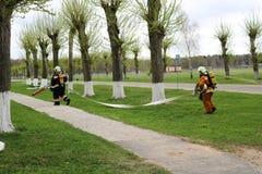Les sapeurs-pompiers professionnels, les sauveteurs dans les costumes ignifuges protecteurs, les casques et les masques de gaz se photos stock