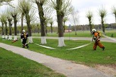 Les sapeurs-pompiers professionnels, les sauveteurs dans les costumes ignifuges protecteurs, les casques et les masques de gaz se images stock