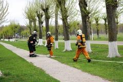 Les sapeurs-pompiers professionnels, les sauveteurs dans les costumes ignifuges protecteurs, les casques et les masques de gaz se photographie stock