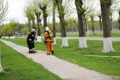Les sapeurs-pompiers professionnels, les sauveteurs dans les costumes ignifuges protecteurs, les casques et les masques de gaz se photo libre de droits