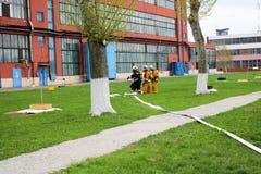 Les sapeurs-pompiers professionnels, les sauveteurs dans les costumes ignifuges protecteurs, les casques et les masques de gaz se image stock
