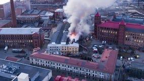 Les sapeurs-pompiers s'éteignent un bâtiment brûlant, vue aérienne image libre de droits