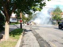 Les sapeurs-pompiers s'éteignent un feu dans un voisinage résidentiel image libre de droits
