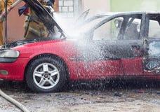 Les sapeurs-pompiers s'éteignent une voiture brûlante avec de l'eau, mettent le feu, s'éteignent image libre de droits
