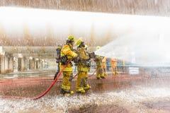 Les sapeurs-pompiers s'exerçant, premier plan est baisse de sauteur de l'eau images stock