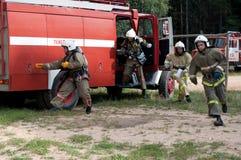 Les sapeurs-pompiers sautent et courent de la cabine du camion de pompiers photographie stock