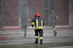 Les sapeurs-pompiers sous éclabousse de l'eau photo libre de droits