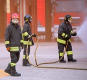 Les sapeurs-pompiers team pendant s'éteindre d'un feu photo libre de droits