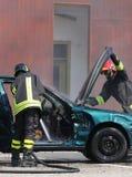 Les sapeurs-pompiers vérifient la voiture d'incident après l'accident de voiture image stock