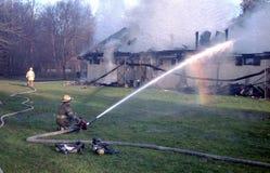 Les sapeurs-pompiers versent l'eau sur un bâtiment sur le feu images stock