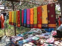 Les saris colorés sont en vente au marché hebdomadaire Photos libres de droits