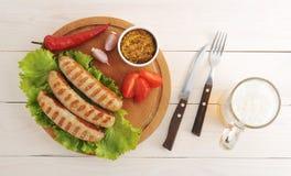 Les saucisses bavaroises ont grillé sur un conseil et une bière ronds en bois Photographie stock libre de droits