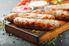 Les saucisses frites avec des sauces et des herbes sur une portion en bois embarquent Grand casse-croûte de bière sur un fond fon photos stock