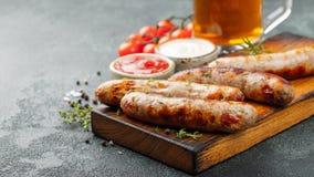 Les saucisses frites avec des sauces et des herbes sur une portion en bois embarquent Grand casse-croûte de bière sur un fond fon photos libres de droits