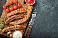 Les saucisses frites avec des sauces et des herbes sur une portion en bois embarquent Grand casse-croûte de bière sur un fond fon photographie stock