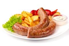 Les saucisses grillées avec des fritures de pommes de terre solated sur le fond blanc Image stock