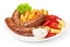 Les saucisses grillées avec des fritures de pommes de terre solated sur le fond blanc Photo libre de droits