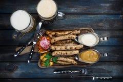 Les saucisses grillées avec une tasse de bière avec des pommes de terre sauce et des couverts sur un conseil en bois image stock