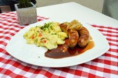 Les saucisses grillées de pays ont servi avec des pommes de terre dans salé Image libre de droits