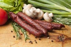 Les saucisses sur un conseil en bois, se ferment  Photos stock