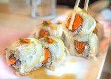 Les saumons éclaboussent le foyer sélectif de petit pain de sushi du fond brouillé Photos libres de droits