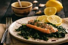 Les saumons cuits au four ont servi sur les épinards cuits avec de la sauce à beurre de citron photographie stock libre de droits