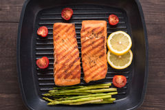 Les saumons grillés ont fait cuire le BBQ sur une casserole sur le fond en bois Photos stock