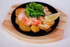 Les saumons ont fait cuire au four avec les pommes de terre et le citron sur une poêle de fonte Photographie stock